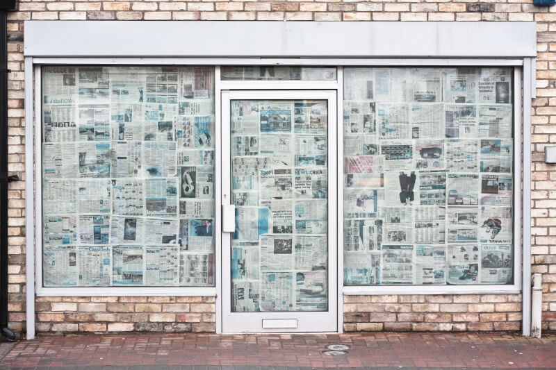 image of store front covered in newspapers