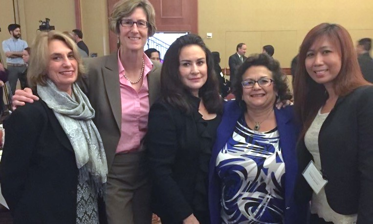 Sandra stands with four friends at a conference, the women have their arms around eachother and are wearing black blazers